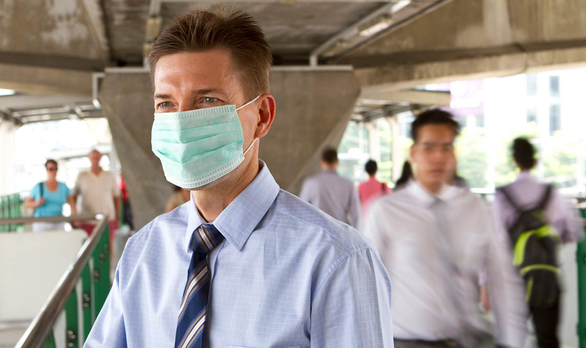 adult male wearing surgical mask to prevent virus exposure
